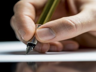 Close up of the hand of a man writing a letter or notes with a fountain pen on a sheet of paper or signing a document or contract