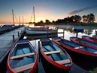 boats and yachts on lake at misty sunrise