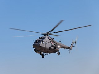 The military helicopter against the blue sky